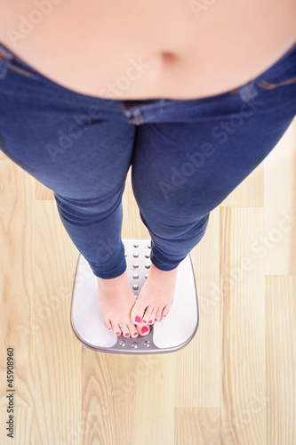 Woman on a bathroom scale hiding the numbers