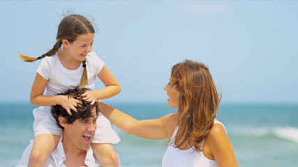 Caucasian girl being carried on fathers shoulders on beach
