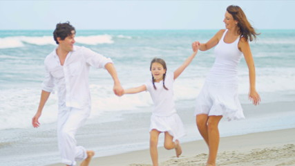 Caucasian parents walking holding hands young daughter by ocean