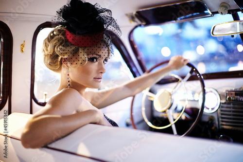 beautiful fashion girl in retro style sitting in old car