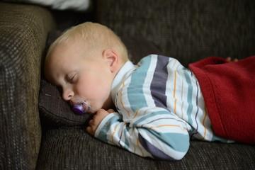 Kleinkind mit Schnuller schläft auf dem Sofa