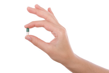 Hand holding a capsule or pill isolated on white
