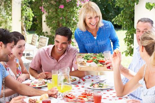 Group Of Young And Senior Couples Enjoying Family Meal