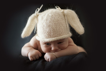 cute newborn baby bunny in the cap on a black background