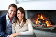 canvas print picture - Romantic couple sitting by fireplace at home