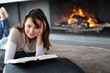 Portrait of beautiful woman reading book by fireplace