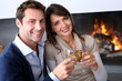 Cheerful couple drinking champaign by fireplace