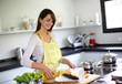 Woman in kitchen preparing fish dish