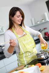 Woman in kitchen preparing pasta dish