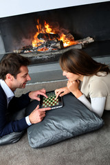Couple sitting by fireplace and playing game with tablet