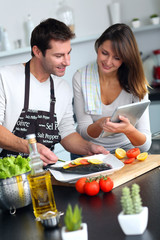 Couple in home kitchen using electronic tablet