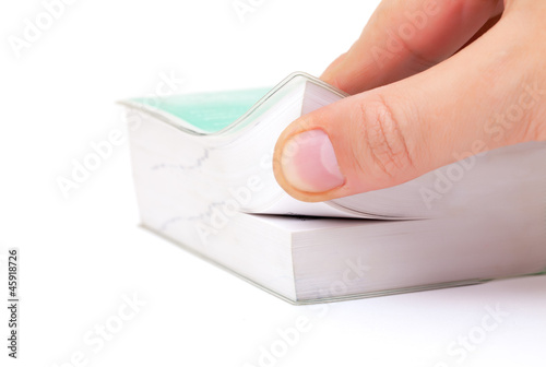 Person thumbing the pages of a book