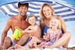 Family Sheltering From Sun Under Beach Umbrella