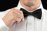 Man In Tux Straightens Bowtie, One Hand poster