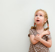 Portrait of little girl standing against the wall and looking up