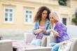 two teen woman friends having fun sitting in outdoor cafe