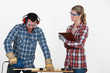 Man sawing a plank and woman supervising work