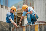 Two construction workers installing concrete formwork frames poster