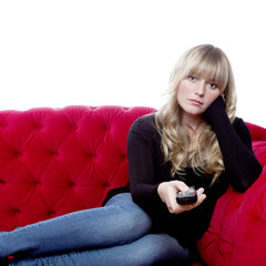 young blond haired girl on red sofa with remote control
