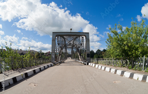 Old arched metal bridge in Novgorod region, Russia.