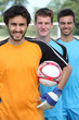 Three smiling footballers with ball
