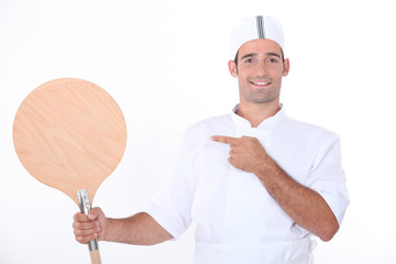 Man holding up a pizza peel