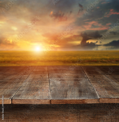 Wooden table with rural scene in background