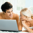 Cheerful couple with laptop, at home