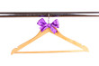 Beautiful purple bow hanging on wooden hanger isolated on white