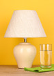 table lamp and glass of water on yellow background