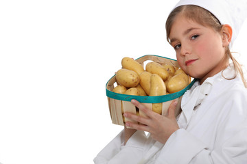 Little girl with a basket of new potatoes