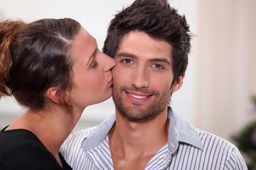 Woman kissing man on the cheek