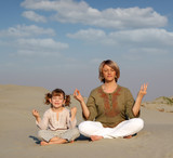 mother and daughter meditating in desert