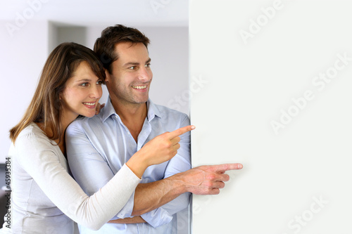 Cheerful couple looking at message on whiteboard