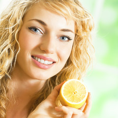 Young happy smiling woman with lemon