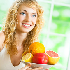 Cheerful smiling blond woman with fruits