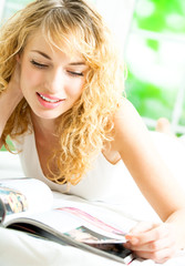 Cheerful blond woman reading magazine