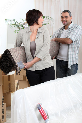 Couple carrying rolled-up carpet