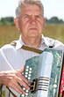 Grandfather play on accordion in field, closeup