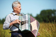 Grandfather in shirt play on accordion in field, halfbody