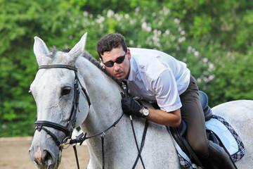 Jockey in glasses with whip hug horse on hippodrome