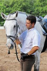 Jockey in gloves hug horse on hippodrome