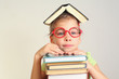 Little girl in glasses with book on head, hands on books