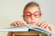 Little girl in red glasses read book