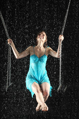Sexy girl riding on swing hold for chain lokking up under rain