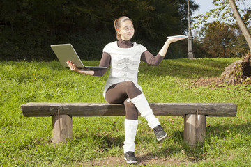 Cute girl in dilemma what to use, laptop or Tablet PC