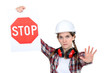 A road worker holding a stop sign.