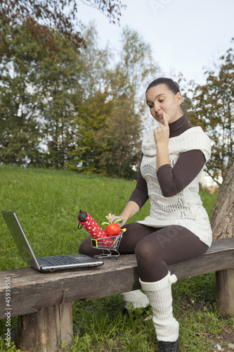 Concept of online shopping - cute girl thinks what to shop