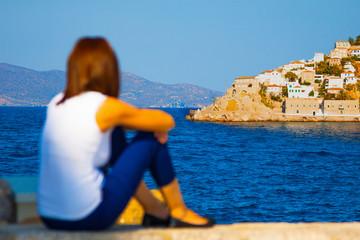 Woman looking at Hydras port in Greece Saronikos Gulf.