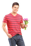Smiling man holding a bunch of tulips
